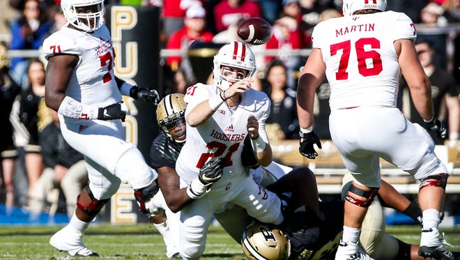 Indiana quarterback Richard Lagow tosses the ball while being tackled during the 93rd playing of the Old Oaken Bucket game at Ross-Ade Stadium in West Lafayette, Ind. on Saturday, November 25, 2017.