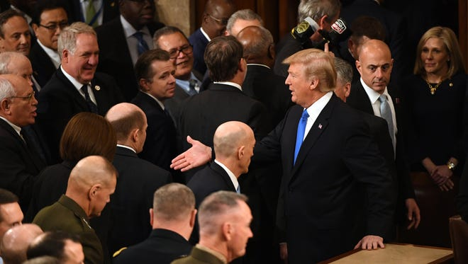 President Donald Trump shakes hands with members of congress after delivering the State of the Union address on Jan. 30, 2018 from the House chamber of the United States Capitol in Washington.