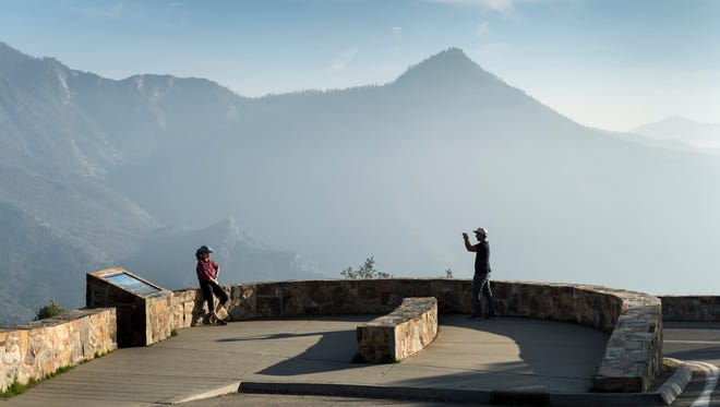 First-time park visitors Bradlee Locke, left, and Andrew Retire of Riverside stop for pictures at Amphitheater Point in Sequoia National Park on Monday, February 5, 2018. The mountain tops in the background are usually still covered in snow this time of year.