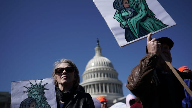 Immigration activists hold signs during a protest March 5, 2018 on Capitol Hill in Washington, D.C.