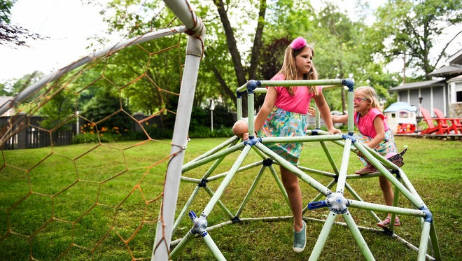 Madison Barber, 7, and her sister Sullivan, 6, play in their back yard on Thursday, May 31, 2018. Barber has fully recovered from an ankle break on a family trip after receiving care at the Injury Care Clinic at Shriners Hospital for Children.