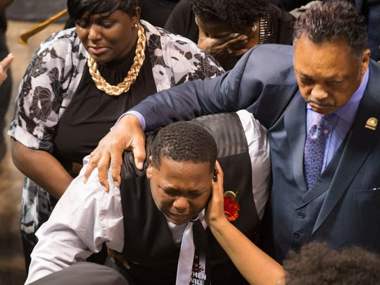 Cameron Sterling, the son of Alton Sterling, is consoled by Rev. Jesse Jackson and a family member during his father's funeral at Southern University in Baton Rouge July 15, 2016. Sterling was fatally shot in scuffle with police July 5.