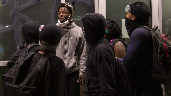 August Montana, an LCC student, center, confronts fellow protesters late Saturday night as they try to break window at Whole Foods in Eugene. [Chris Pietsch/The Register-Guard] - registerguard.com