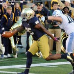 Notre Dame running back Taraen Folston (left) scores a touchdown in front of North Carolina's Jeff Schoettmer in Notre Dames' 50-43 win Saturday. Folston had 18 carries for 98 yards and two touchdowns.