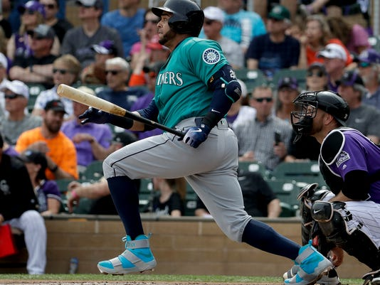 Seattle Mariners' Nelson Cruz watches his RBI-single against the Colorado Rockies during the first inning of a spring training baseball game in Scottsdale, Ariz., Tuesday, March 13, 2018. (AP Photo/Chris Carlson)