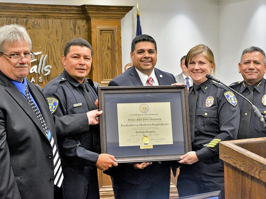 Decatur Police Chief Rex Hoskins (left) presents a certification of re-recognition from the Best Practices program of the Texas Police Chiefs Association Foundation to the Wichita Falls Police Department during Tuesday's city council meeting. Also picture, from left: Officer Charles Casillas, Mayor Stephen Santellana, Lt. Ginger Gilmore and Police Chief Manuel Borrego.
