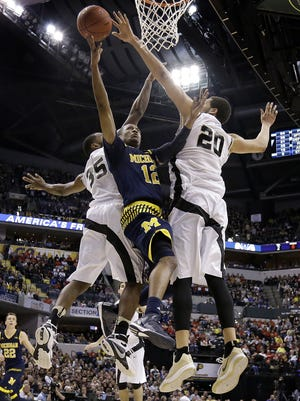 Purdue Boilermakers center A.J. Hammons (20) blocks the shot by Michigan Wolverines guard Muhammad-Ali Abdur-Rahkman (12) in the second half of their Big Ten Men's Basketball Tournament semifinal game Saturday, Mar 12, 2016, afternoon at Bankers Life Fieldhouse. The Purdue Boilermakers defeated the Michigan Wolverines 76-59.