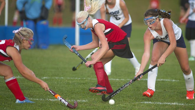 From left, CVU's 12 Nicole Anderson and Kelsie Saia try to beat MMU's #5 Perry Willett to the ball during their high school field hockey game earlier this season.