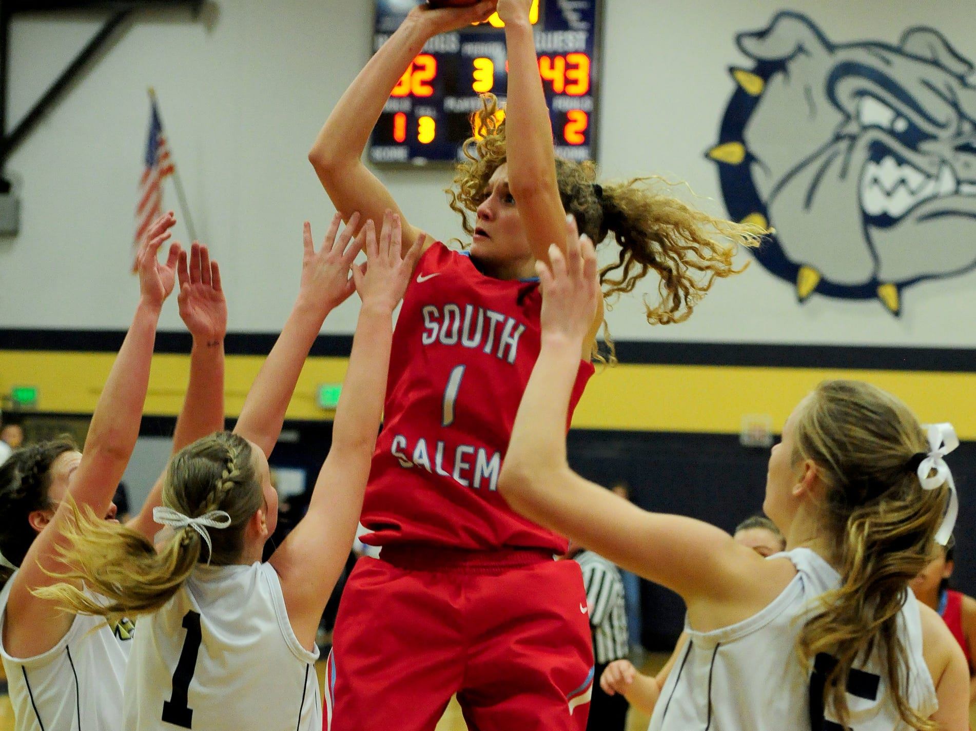 South Salem guard Katie McWilliams with a shot over a trio of West Albany defenders during a Greater Valley Conference game on Tuesday, February 24, 2015, in Albany.
