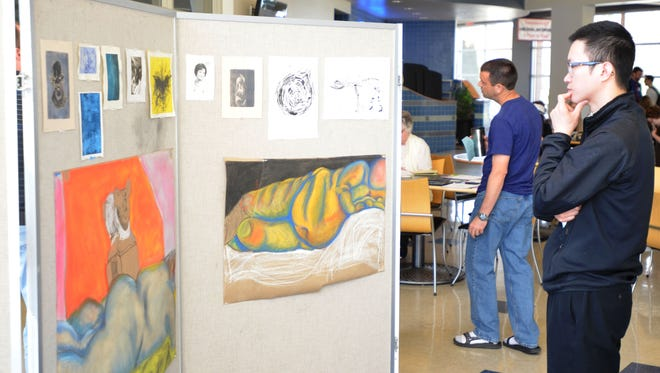 Juliang Lai admires student artwork on display during the inaugural Campus Research and Creative Activities Symposium at UW-Manitowoc on Friday.