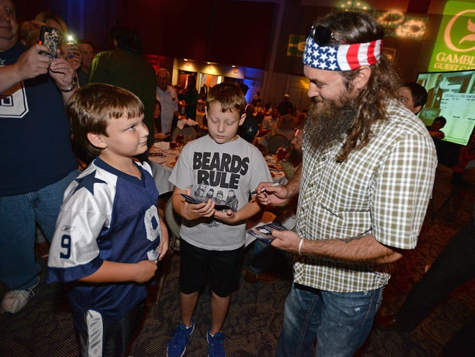 Willie Robertson of Duck Dynasty signs an autograph for Chase McGough (center) and Jacob Gardner of West Monroe while attending the Duck Commander Independence Bowl Kickoff Luncheon Wednesday afternoon at the Shreveport Convention Center.