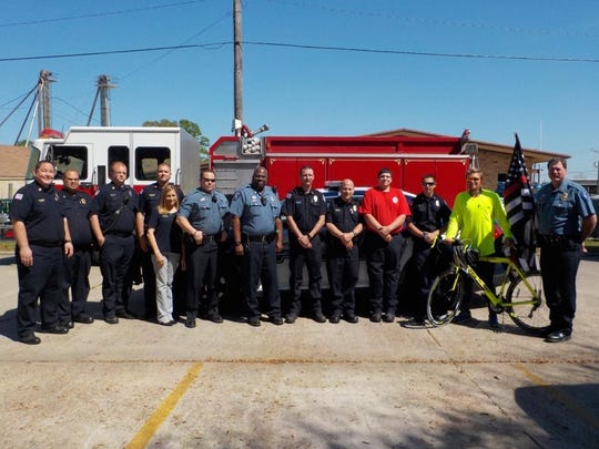 Aodhan O'Ferrell (with bicycle) poses with first responders in DeRidder last month.