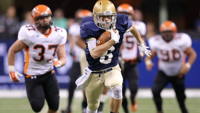Cathedral wide receiver James Schulz breaks a tackle and sprints to the end zone for a touchdown against LaPorte in the IHSAA Class 5A State Football Finals at Lucas Oil Stadium on Saturday, Nov. 29, 2014.