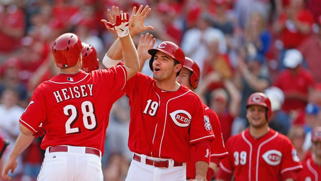 Cincinnati Reds Chris Heisey, 28, is congratulated by Joey Votto and other teammates as he crosses the plate following his grand slam off Tampa Bay Rays Josh Lueke at Great American Ball Park on April 13.