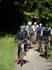 FILE — Julie Snyder of the Evergreen Mountain Bike Alliance leads a group through trails in the Port Gamble Heritage Park. More trails will be constructed this summer with money from the Kitsap Public Facilities District.
