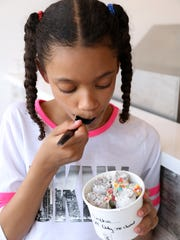 Sophia Nix, 9, of Mamaroneck eats rolled ice cream