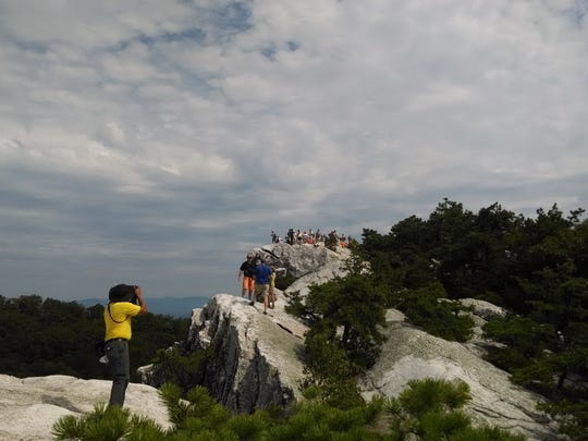 A group of Poughkeepsie Journal readers take part in a hike and pose for a photo at the top of Bonticou Crag on July 26, 2014.