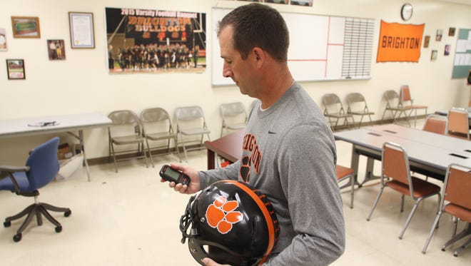 Brighton High School varsity football Coach Brian Lemons holds a Riddell Insite, a hand-held deviced used to track high-impact hits during football games and practices.