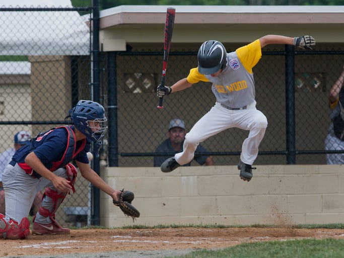 Connecticut's Zach Bartalome jumps high to avoid a wild pitch that went all the way to backstop allowing John McPhee to score in the second inning. Parsippany-Troy East Junior Baseball vs Connecticut in Regional Tournament play in Freehold on August 2, 2014 - Peter Ackerman / Staff Photographer