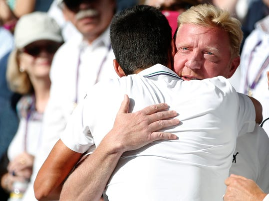 Novak Djokovic of Serbia celebrates with his coach Boris Becker, right, in the players box after defeating Roger Federer of Switzerland in the men's singles final at the All England Lawn Tennis Championships in Wimbledon, London, Sunday July 6, 2014. (AP Photo/Pavel Golovkin)