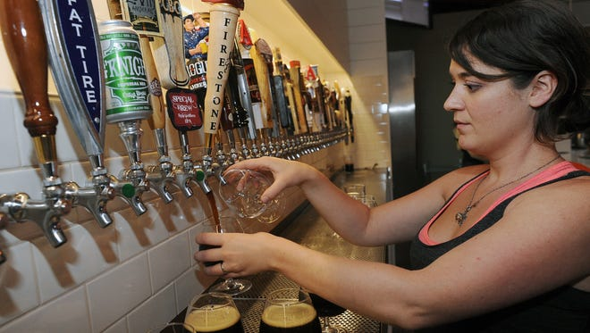 Mayor of Old Town bar manager Michelle Peth fill glasses with Firestone Waker's 15th anniversary in 2012.