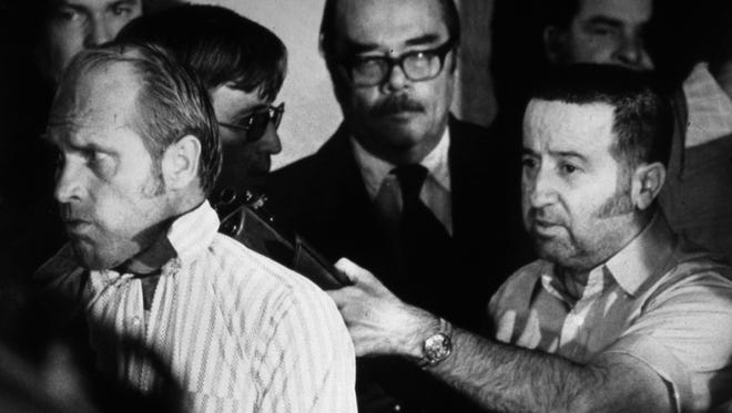 A disgruntled Tony Kiritsis held a shotgun to the head of Richard Hall, president of Meridian Mortgage Co., on Feb. 10, 1977 during the third day of a tense standoff. Fred Heckman of WIBC (in glasses and mustache) served as a go-between with Kiritsis and police.