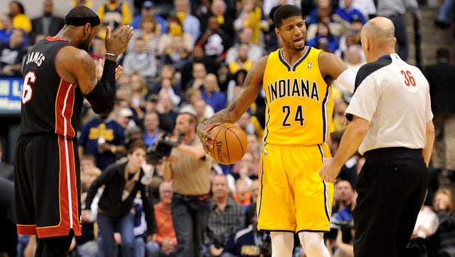 Indiana Pacers forward Paul George pleads his case with an official as Miami Heat forward LeBron James claps as a timeout was called.