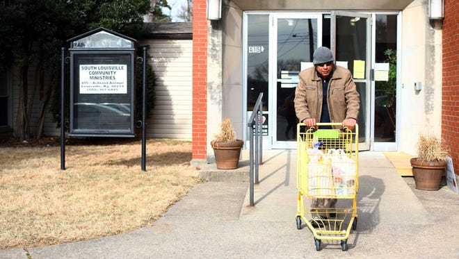 Samir Ali pushes a cart of groceries for a friend out of the South Louisville Community Ministries location at Beechmont Presbyterian Church.