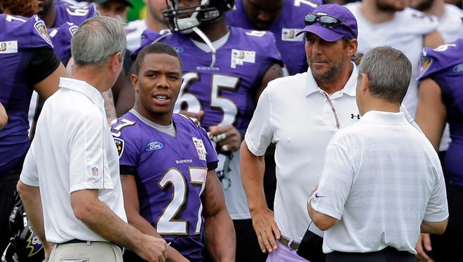 FILE - In this July 24, 2014, file photo, Baltimore Ravens running back Ray Rice, second from left, speaks with team president Dick Cass, left, owner Steve Bisciotti, right, after a training camp practice in Owings Mills, Md. The Ravens have cut Ray Rice. Hours after the release of a video that appears to show Rice striking his then-fiancee in February, the team terminated his contract Monday, Sept. 8, 2014.