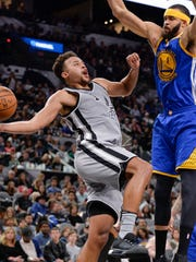 San Antonio Spurs forward Kyle Anderson, left, attempts to shoot against Golden State Warriors center JaVale McGee during the second half of an NBA basketball game, Saturday, March 11, 2017, in San Antonio. San Antonio won 107-85. (AP Photo/Darren Abate)