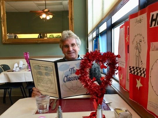 Joel Stratte-McClure with menu at the Classroom restaurant during Valentines week.