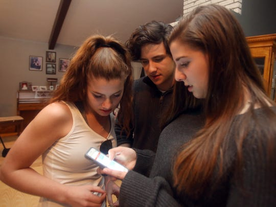 Angela McDevitt, 17, a student at Arlington High School, right, looks at text messages with her friends Rebecca Campos and Spencer Koonin, both 16. McDevitt is being credited with thwarting a possible mass school shooting. McDevitt, photographed Feb. 20, 2018, received text messages from Jack Sawyer, who she had met while both were residents in a Maine treatment center for youths with emotional problems. The text messages she received from Sawyer described his desire to conduct a mass shooting at his old high school in Vermont. McDevitt brought the texts to the attention of authorities, and Sawyer was arrested before he could carry out a shooting.