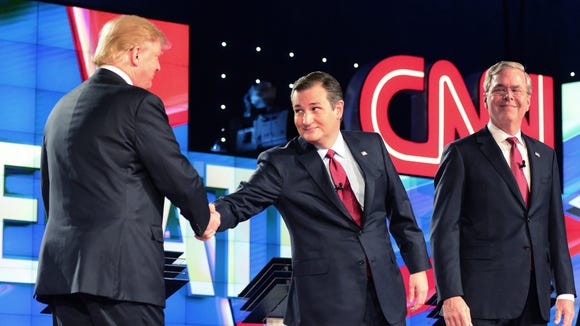 Ted Cruz reaches over to shake Donald Trump's hand as Jeb Bush looks on prior to the beginning of the debate in Las Vegas on Dec. 15, 2015.