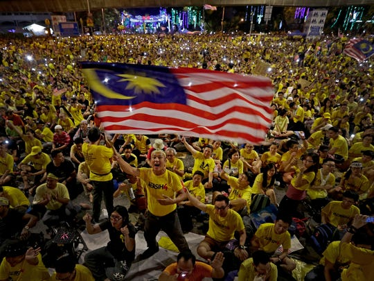 A Malaysian protestor waves the national flag while