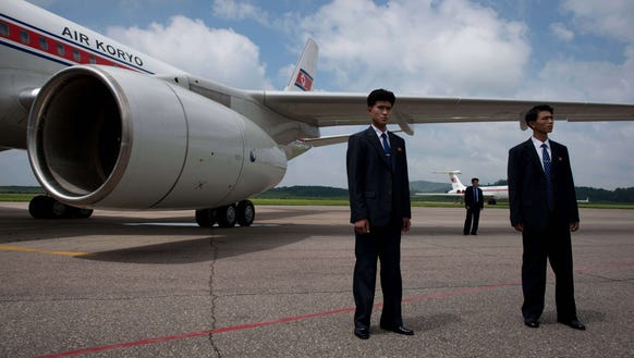 Government minders stand before an Air Koryo aircraft
