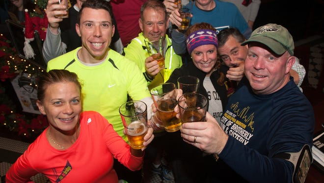 Haddon Hashers runners, Michelle Friedman, left, and  Pat Curley, right cheer along other runner at the P.J. Whelihan's Pub and Restaurant in Haddonfield. The Haddon Hashers get together once a month to run, drink, and run some more.