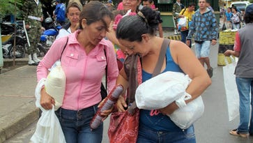 People look through their purchases during admission of Venezuelan citizens to Colombia to buy food and medicine Saturday in Cucuta, Colombia.