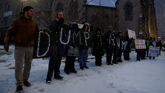 Demonstrators hold banners forming the words 'DUMP