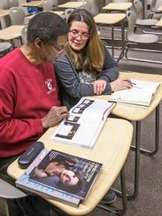 Kim Davis gets help with his reading by literacy tutor Susan Penn.