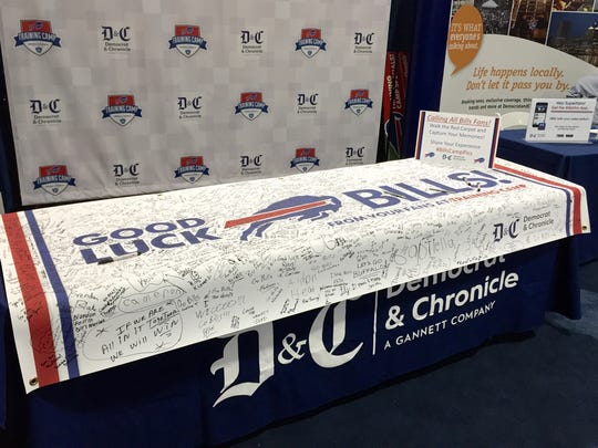 Bills fans sign a good luck banner at the Democrat and Chronicle's table.