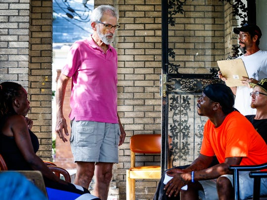 Constance Abbey's co-founder Roger Wolcott (middle) speaks with several people form the neighborhood, who come to his community home for help.