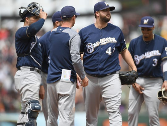 Brewers manager Craig Counsell takes the ball from