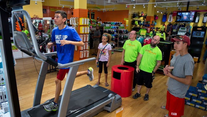 Alex Bagby, 13, left, runs on a treadmill to test his new running shoes while store assistants and his family watch in Fit2Run at Coconut Point Mall in Estero, Fla., on Monday, Dec. 26, 2016. Holiday sales and returns surge after Christmas, bringing in crowds of shoppers.