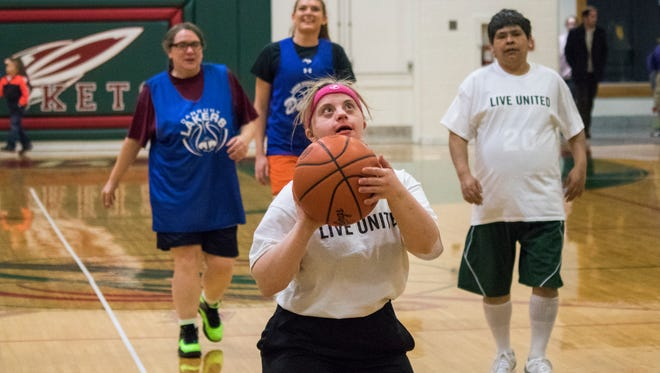 Elizabeth Young, playing for the United Way team, lines up a shot during the 'Can Do! Like You!' basketball tournament.