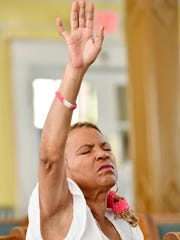 June Lewis raises her hand in praise during worship