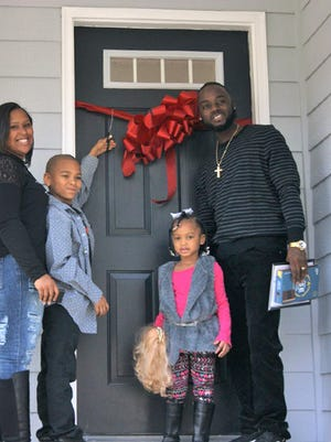 Jarvis and Tiarra Williams, along with their children Jaylen and Janiyah, take ownership of their new home on Chester Road thanks to Habitat for Humanity.