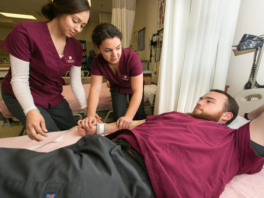 Araceli Sosa, 22, left, and Bianca Holguin, 19, work on restraint training with classmate Manuel Barron, 20, at New Mexico State University. The students are learning about hospital safety.