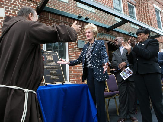 Brother Ronald Giannone gives Julie Cawley a hug after the unveiling of the plaque dedicating the new Sacred Heart Village II building to her and Charles Cowley.