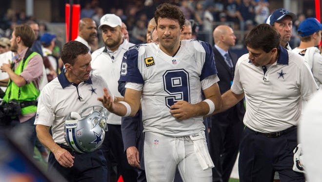 Dallas Cowboys quarterback Tony Romo (9) leaves the game with an injury during the second half of an NFL game against the Carolina Panthers on Thanksgiving at AT&T Stadium.