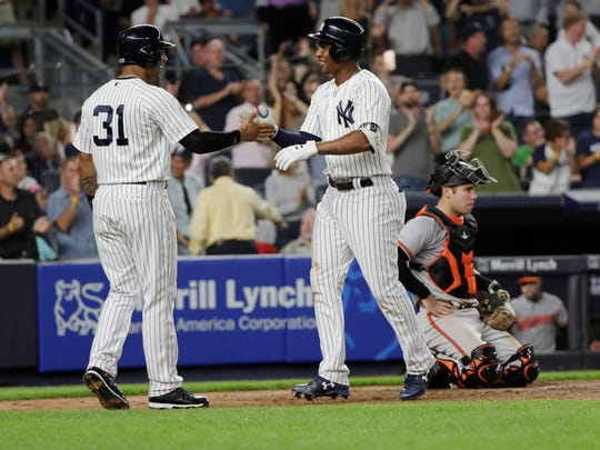 New York Yankees' Aaron Hicks, left, celebrates with teammate Miguel Andujar after they scored on a an Andujar three-run home run during the fifth inning of a baseball game Tuesday, July 31, 2018, in New York. Baltimore Orioles catcher Austin Wynns is at right.